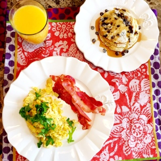 chocolate chip pancakes with powdered sugar, eggs with baby arugula and bacon