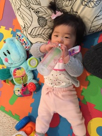 finally starting to hold her own bottles
